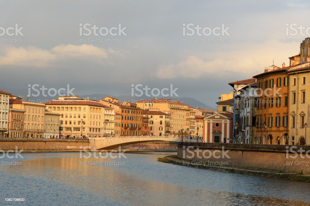 View on embankment of Arno river and bridge Ponte Di Mezzo at sunset. Pisa, Italy stock photo