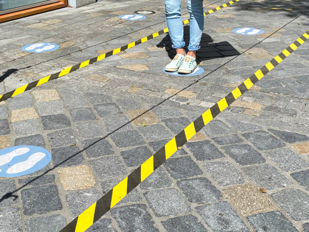 View on feet of one person between do not cross tapes and blue markings to keep distance at shop entrance in corona crisis Roermond, Netherlands - May 19. 2020: View on feet of one person between do not cross tapes and blue markings to keep distance at shop entrance in corona crisis between stock pictures, royalty-free photos & images
