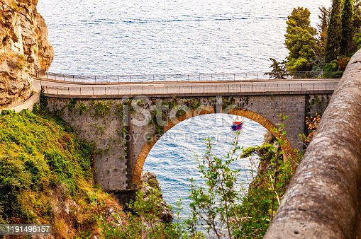 View on Fiordo di Furore arc bridge built between high rocky cliffs above the Tyrrhenian sea bay in Campania region in Italy. Boat floating by the unique cove under the bridge