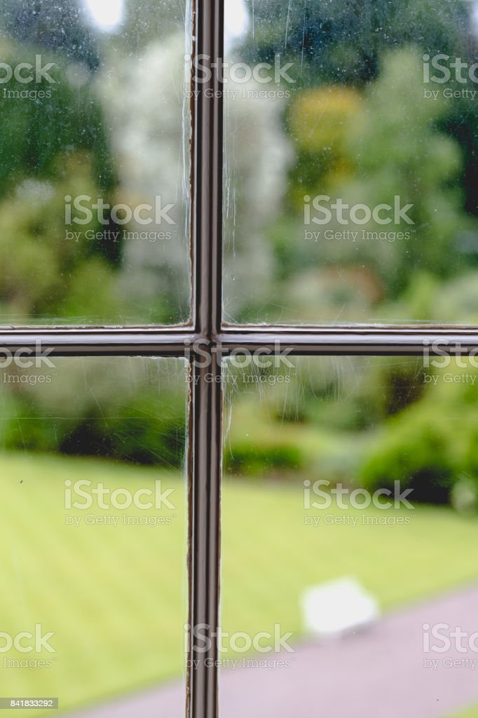 View on green garden through old vintage window with rustic wooden frame stock photo