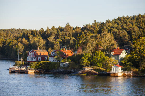 View on luxury cottages with private pier along Stockholm archipelago, Sweden. Summer sunset time. stock photo
