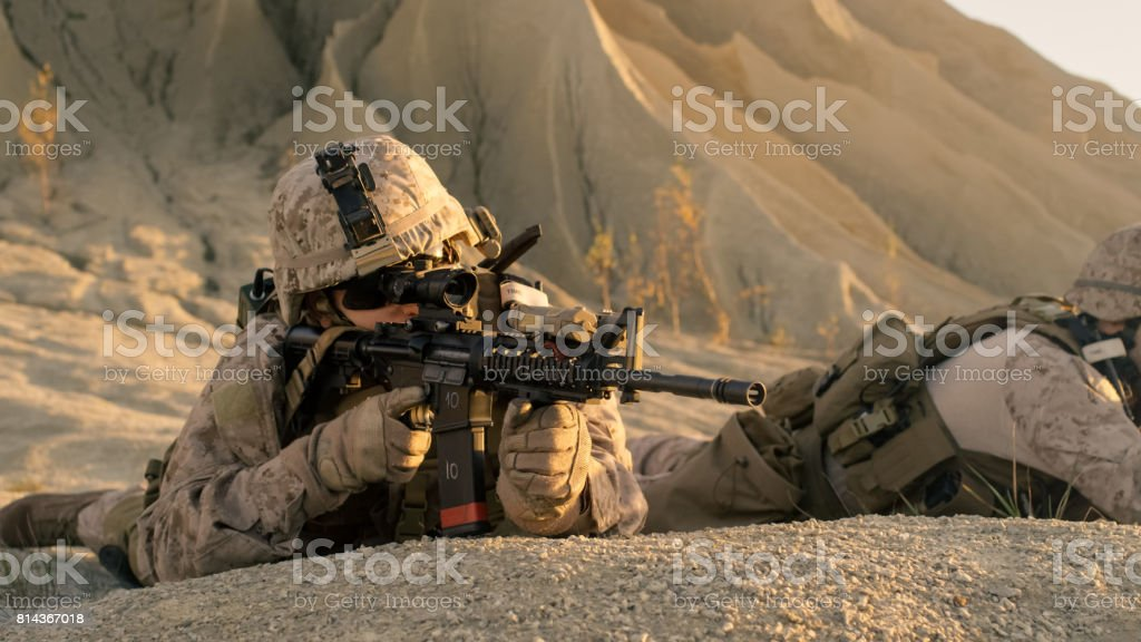 View on Soldier Lying Down on the Hill, Aiming through the Assault Rifle Scope in Desert Environment. stock photo