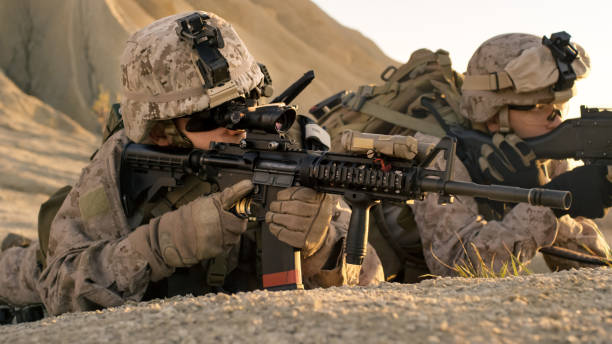 View on Soldiers Lie Down on the Hill, Aim through the Assault Rifle Scope in Desert Environment. stock photo