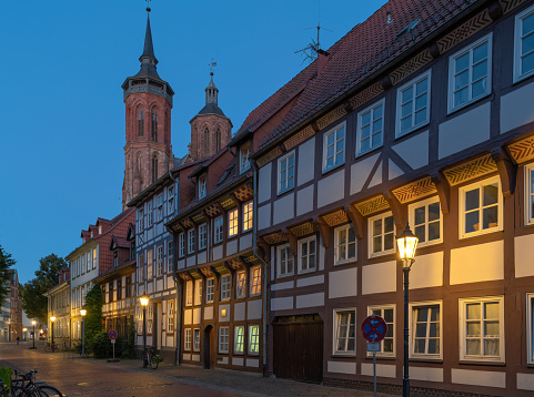 View on St. Johannis church with typical half-timbered houses in twilight at dusk in old town of Goettingen, Lower Saxony, Germany