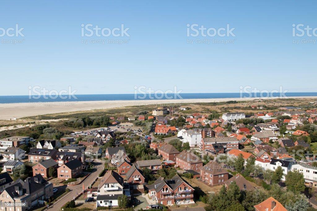 sehen Sie sich auf der Außenseite des Gebäudes mit dem Strand und der Nordsee am Horizont auf der Nordsee-Insel Borkum unter blauem Himmel – Foto
