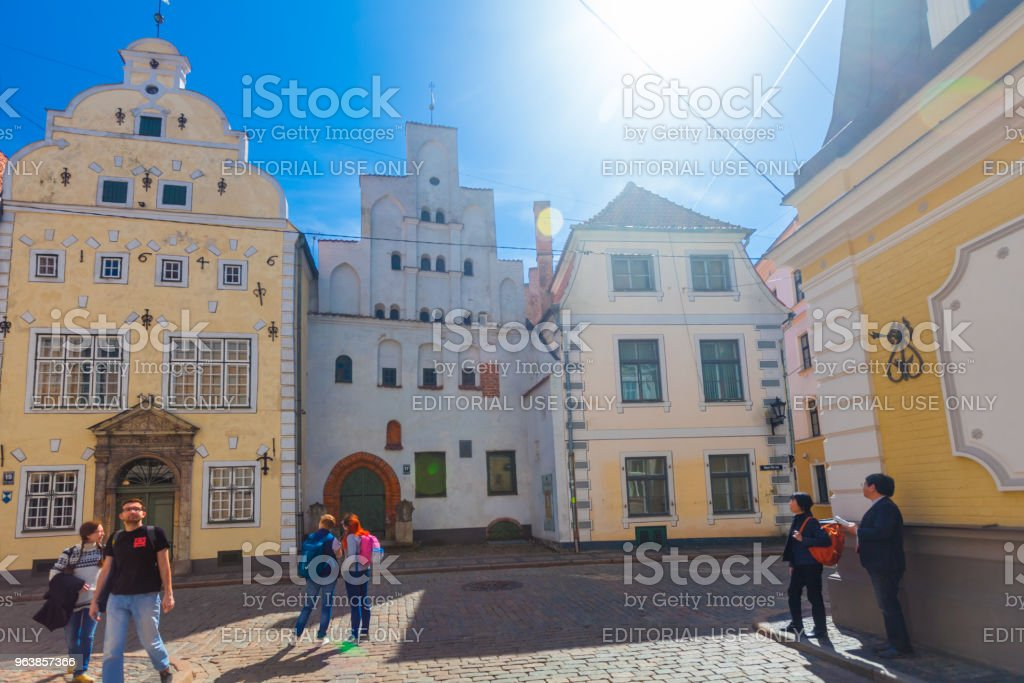 View on the colored cozy old houses and tourists that are located in the city center of Riga. Three Brothers Houses in Riga. Latvia. - Royalty-free Architecture Stock Photo