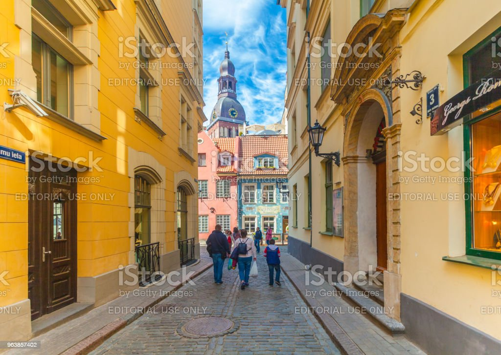View on the colored cozy old houses, church,souvenir street shops and tourists that are located in the city center of Riga. Latvia. - Royalty-free Architecture Stock Photo