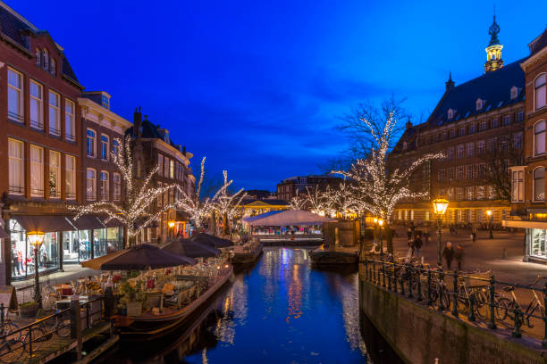 View on the Koorn bridge, people enjoying  Christmas Market in Leiden, the Netherlands people skating on a floating skating-rink on Christmas Market in the old town of Leiden at night. This market is unique in the world because it is a market floating on the water, canal. This image is GPS tagged leiden stock pictures, royalty-free photos & images