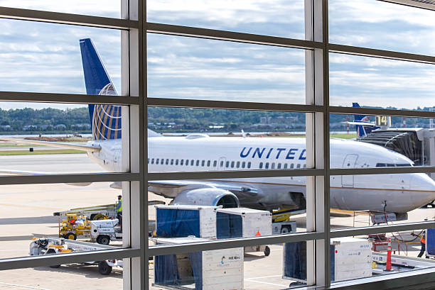 View out airport window to airplanes and ramp operations stock photo