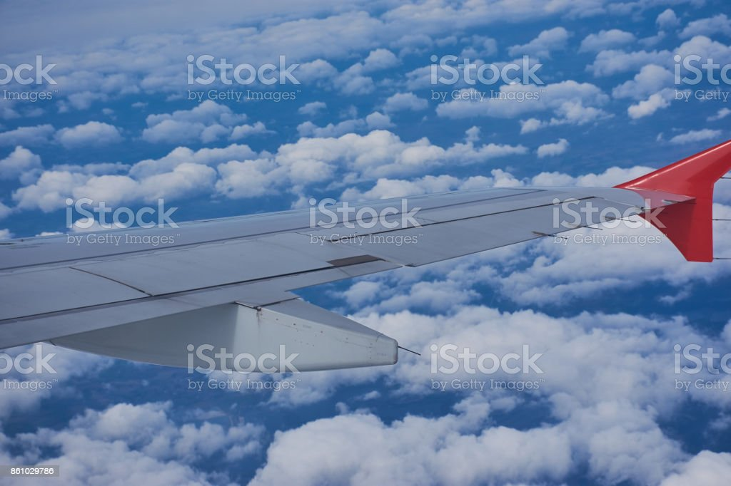 View out of a plane window in a cloudy sky stock photo