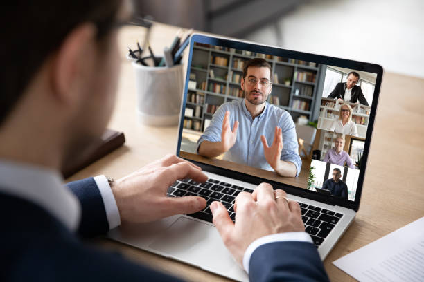 View over businessman shoulder laptop screen and videocall diverse participants stock photo