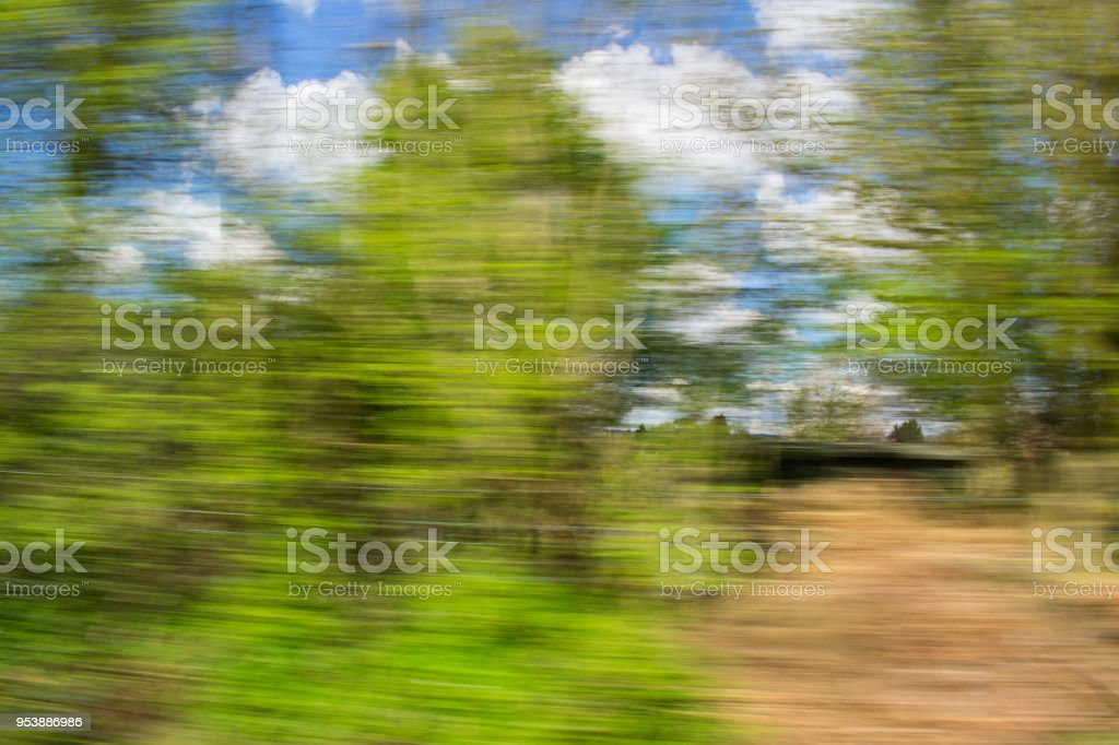 View over car window blurred trees and blue sky with clouds summer time bokeh stock photo