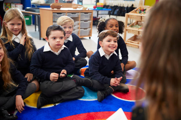 教室の床に足の hercross の前に座って子供たちの小学校の女教師の肩の上を表示します。 - disabilitycollection ストックフォトと画像