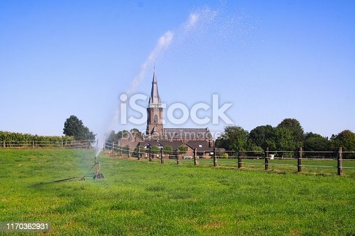 View over green fields with fence and water fountain of agricultural sprinkler system on isolated neo-gothic church in countryside - Viersen Dornbusch, Germany