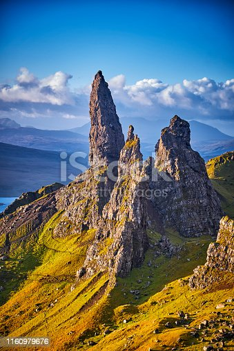 View Over Old Man Of Storr, Isle Of Skye, Scotland. During a beautiful sunrise and dramatic sky with a local shower here and there. The Old Man of Storr looms over Portree, Isle of Skye and is situated 7 miles north of the town. It is dominated by the 50 metre high petrified lava pinnacle of the Old Man of Storr, with a brutal tumble of cliff behind, and the panorama spreads across loch, sea and islands to the high mountains of the mainland beyond.