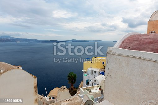 A high level view over rooftops and paint washed buildings towards the caldera and neighbouring islands from a high vantage point in Oia on the Greek Cyclades island of Santorini.