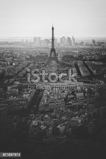 View, in black and white, over central Paris, with the Eiffel tower in the distance, and La Defense business district beyond.