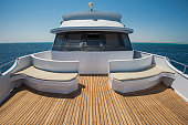 View over the bow of a large luxury motor yacht on tropical open ocean with bridge cabin