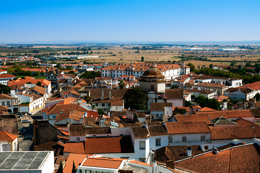 View over the city of Evora in the Alentejo province of Portugal. Whitewashed walls and terracotta roof tiles in the foreground, open countryside in the mid distance, mountains on the horizon and a clear blue sky overhead.