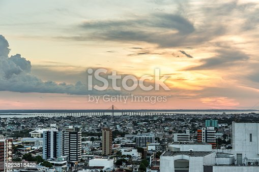 Aerial view at sunset with a beautiful cloudy sky over the urban city of Manaus in the Amazon region of north Brazil in South America, with high rise buildings & the Rio Negra bridge over the Rio Negra river in the background