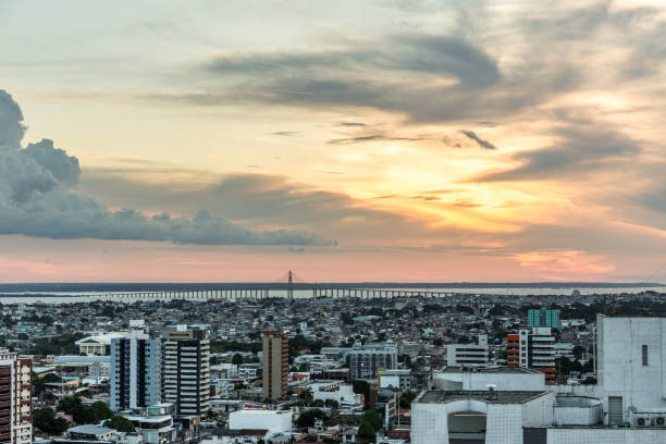 View over the city of Manaus at sunset with Rio Negra bridge in background in Amazon region of Brazil, South America Aerial view at sunset with a beautiful cloudy sky over the urban city of Manaus in the Amazon region of north Brazil in South America, with high rise buildings & the Rio Negra bridge over the Rio Negra river in the background manaus stock pictures, royalty-free photos & images
