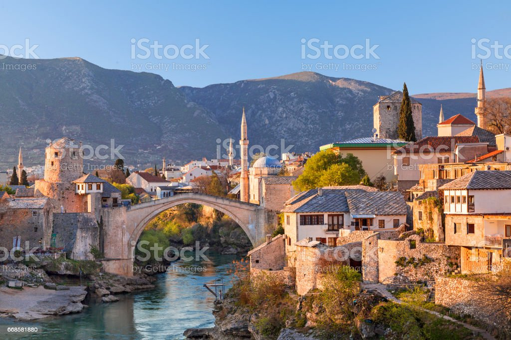 View over the city of Mostar with Mostar Bridge, houses and minarets, at the sunset, in Mostar, Bosnia Herzegovina. stock photo