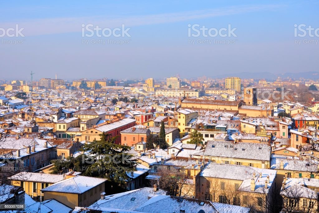 View over the city rooftops with sunlight and snow. Brescia, Italy. - foto stock