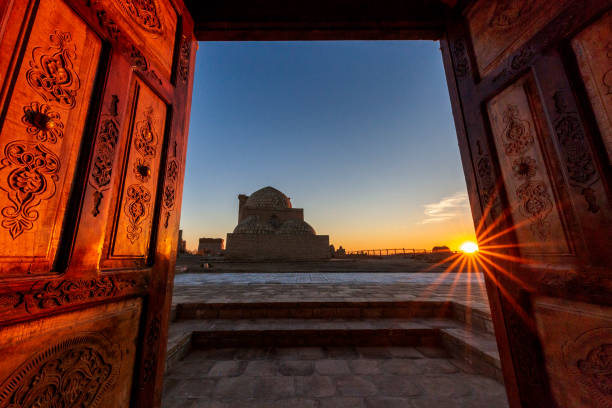 View over the mausolem through wooden doors at the sunset, in the ancient cemetery of Mizdakhan in Nukus, Uzbekistan Historical cemetery of Mizdakhan in Nukus, Uzbekistan silk road stock pictures, royalty-free photos & images