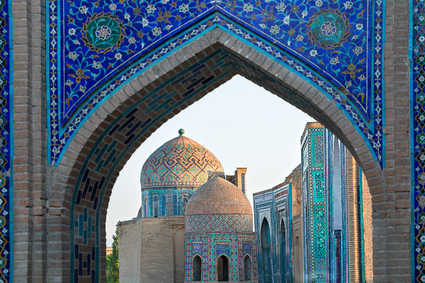 View over the mausoleums and domes of the historical cemetery of Shahi Zinda through an arched gate, Samarkand, Uzbekistan. stock photo
