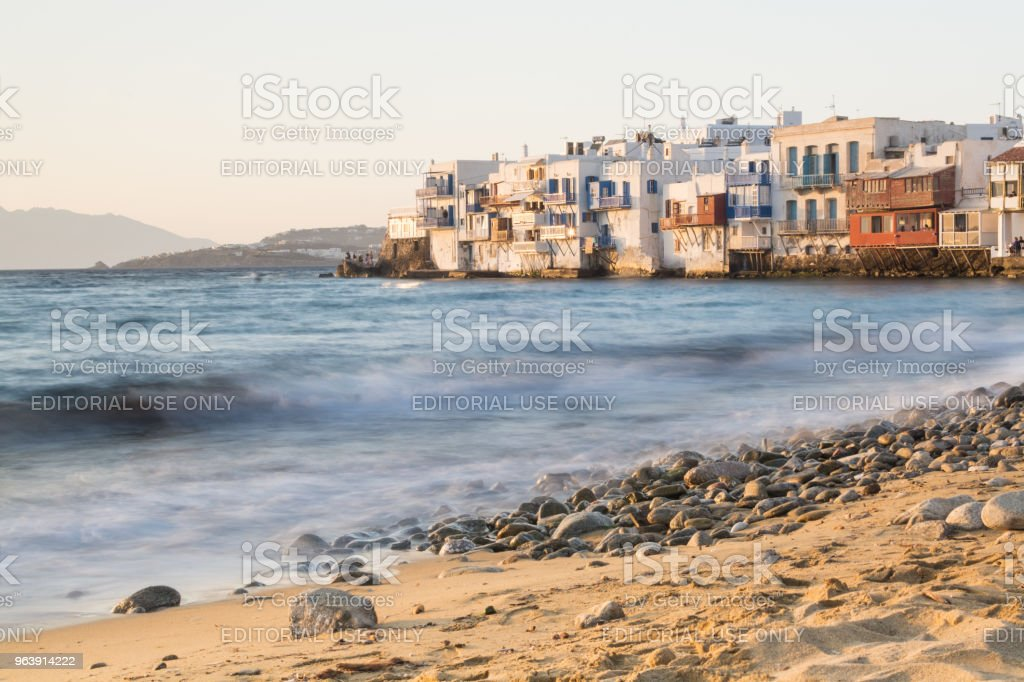 MYKONOS, GREECE - MAY 2018: View over the old Mykonos town district Little Venice with stony beach and sea on the foreground. Long exposure shot, water movement effect - Royalty-free Ancient Stock Photo
