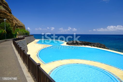 View over the public swimming pool on the coast at Porto da Cruz in the middle of the Atlantic Ocean during a beautiful summer day
