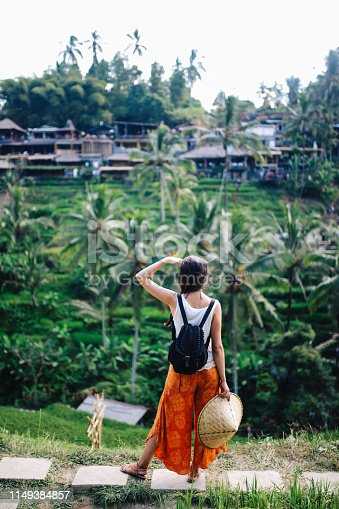 Young solo traveler woman is enjoying the amazing view above the rice terraces, fields in Bali, Indonesia. Tourism, traveling concepts in Southeast Asia, Indonesian culture.
