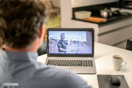 View over unrecognized man's shoulder on laptop computer screen. Man watching online seminar. Home office, working from home, online education concept.