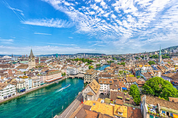 View over Zürich Elevated view over Zürich and the Limmat river with the landmark town hall and a ferry boat on a beautiful summer day. zurich stock pictures, royalty-free photos & images