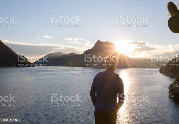 Photo of View past man to lake, sun and mountains
