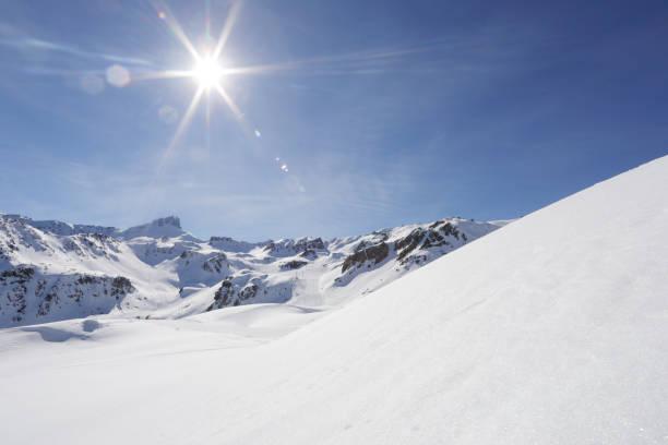 bekijk langs besneeuwde heuvel naar zon en bergen - skipiste stockfoto's en -beelden