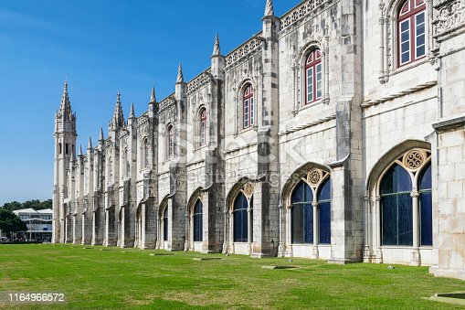 View perspective on the walls of the monastery Jeronimos, against the blue sky, with a green lawn