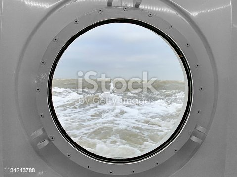 View through a porthole on a stormy sea with waves hitting the ship at the Wadden Sea between Lauwersoog and Schiermmonnikoog
