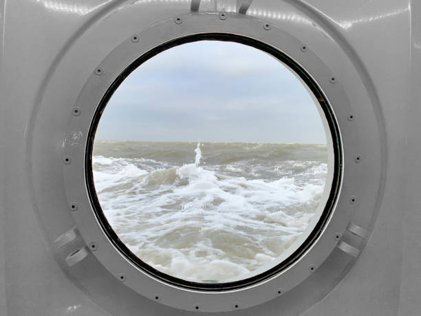 View through a porthole on a stormy sea with waves hitting the ship - foto stock