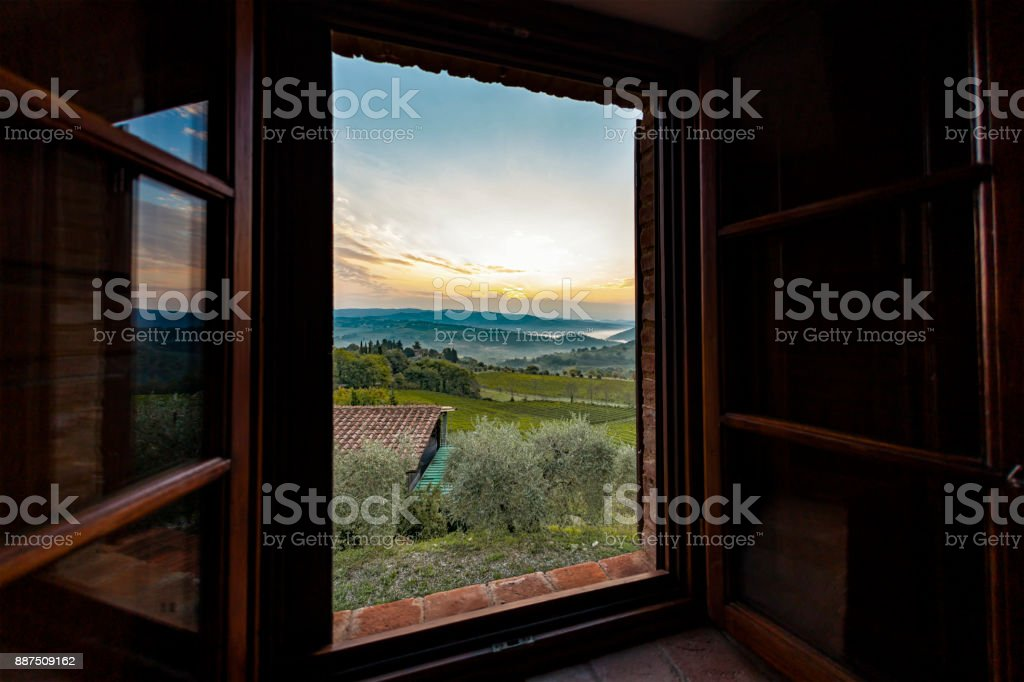 View through a window to a sunrise over foggy hills in Tuscany stock photo