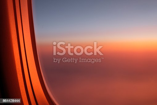 1045890176 istock photo View through airplane porthole of sunset in sky 864428444
