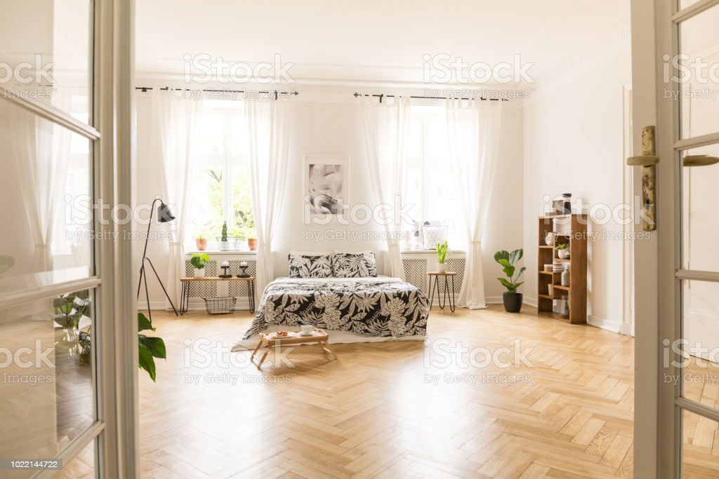 View Through An Open Double Door Into A Bedroom Interior With Wooden Parquet Large Windows And White Walls Bed With Linen Breakfast Tray Lamp And Bookcase In The Room Real Photo Stock