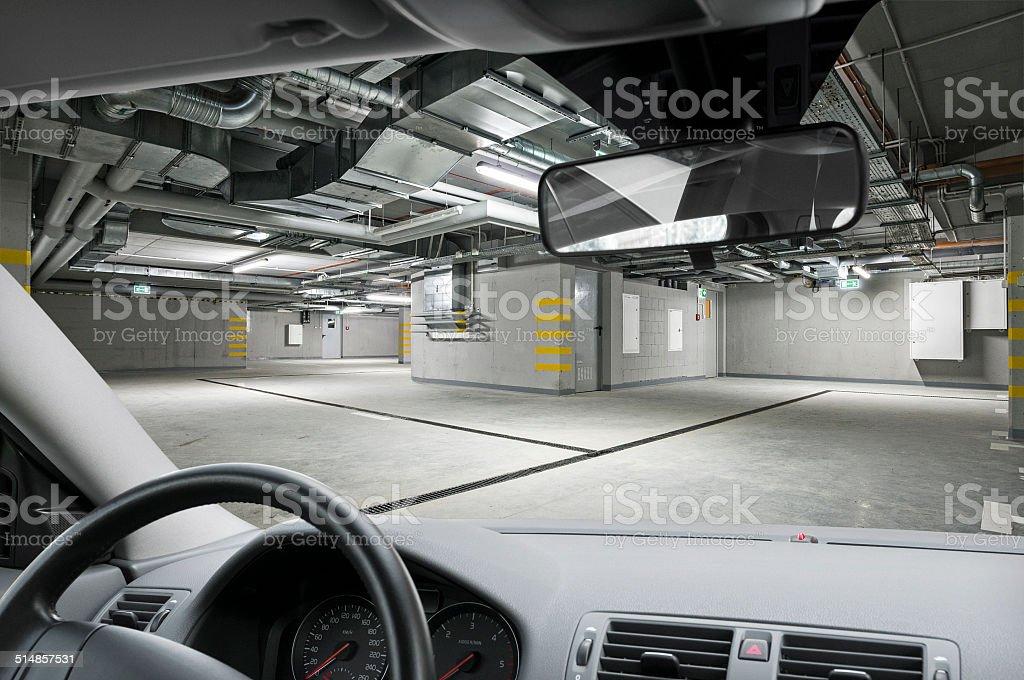 View through car dashboard on empty underground parking garage stock photo