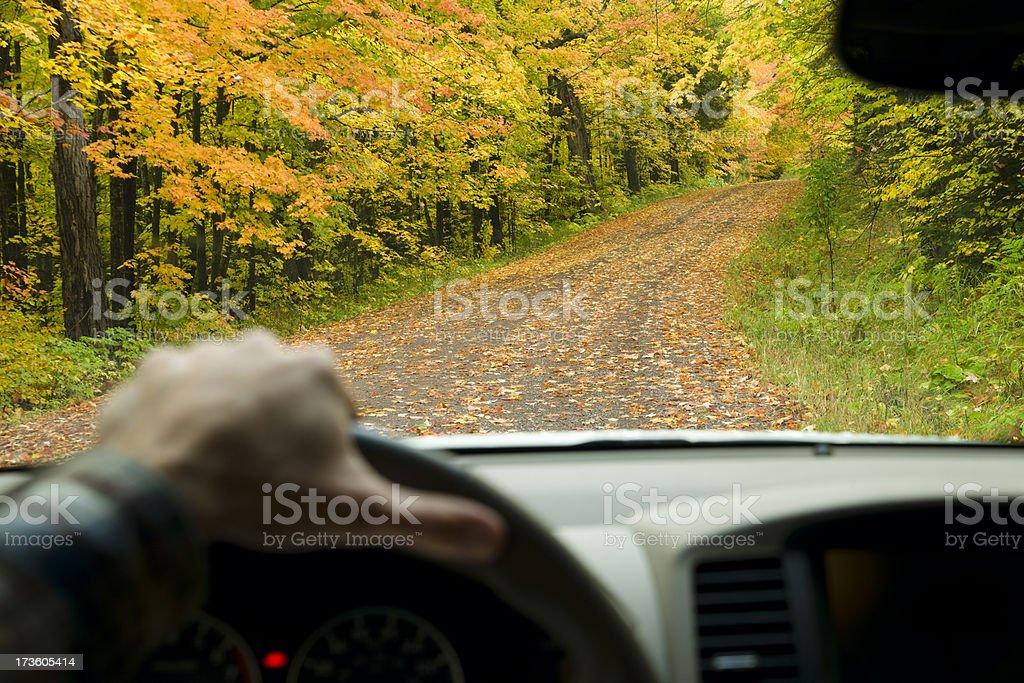 View through car windshield driving along scenic autumn road. royalty-free stock photo