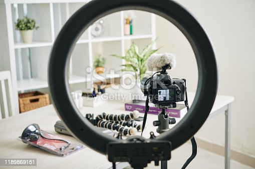 Circle lamp, digital camera and monopods in office of professional blogger