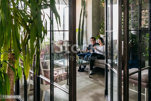 Chinese couple sitting on sofa at home with digital device, open glass door with plants in modern Chinese home