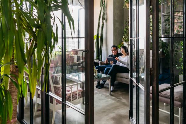 view through conservatory doorway to couple using tablet - оранжерея стоковые фото и изображения
