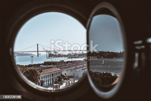 View through a round opened porthole of a traveling cruise ship of a port zone of Lisbon with a suspension bridge and docks in the background, a river with a single sailboat reflecting in the window