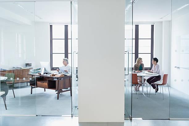 blick durch die glaswand in modernen büro - raumteiler weiß stock-fotos und bilder