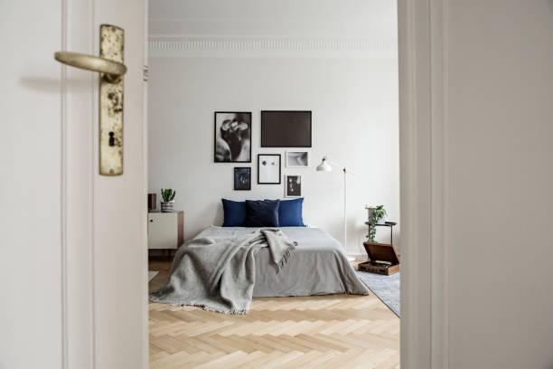 blick durch die offene tür in ein geräumiges und natürliches schlafzimmer mit holzfußboden, kunstgalerie und minimalistischem dekor - marineblau schlafzimmer stock-fotos und bilder